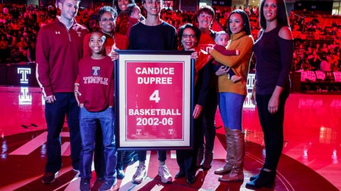 Former Temple player Candice Dupree, center, holds up the frame for her retired number with family and friends around her during halftime of an NCAA college basketball game against South Carolina, Thursday, Dec. 21, 2017, in Philadelphia. (AP Photo/Chris Szagola)