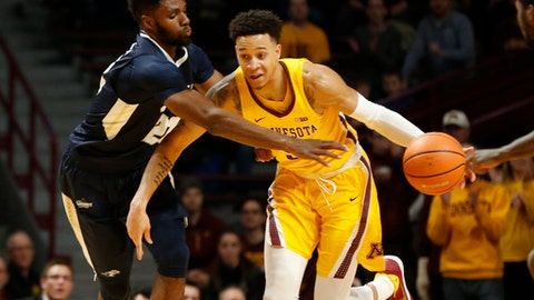 Minnesota's Amir Coffey, right, drives around Oral Roberts' Emmanuel Nzekwesi in the second half of an NCAA college basketball game Thursday, Dec. 21, 2017, in Minneapolis. Minnesota won 77-63. (AP Photo/Jim Mone)