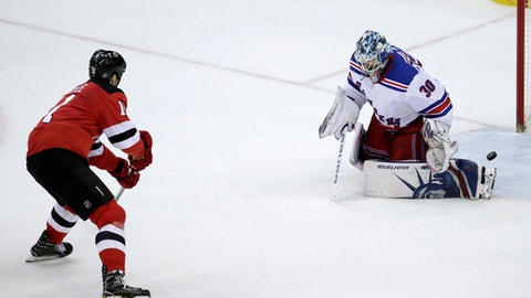 New Jersey Devils center Brian Boyle, left, scores on New York Rangers goalie Henrik Lundqvist, of Sweden, during the shootout in an NHL hockey game Thursday, Dec. 21, 2017, in Newark, N.J. The Devils won 4-3. (AP Photo/Julio Cortez)