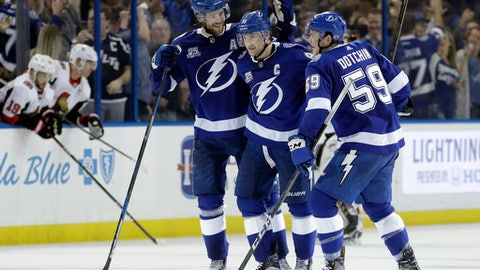 Tampa Bay Lightning center Steven Stamkos (91) celebrates his shootout goal against the Ottawa Senators with defenseman Victor Hedman (77) and defenseman Jake Dotchin (59) during an NHL hockey game Thursday, Dec. 21, 2017, in Tampa, Fla. The Lightning won the game 4-3. (AP Photo/Chris O'Meara)