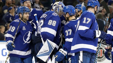 Tampa Bay Lightning goalie Andrei Vasilevskiy (88) is mobbed by teammates, including Cory Conacher (89) center Yanni Gourde (37) and left wing Alex Killorn (17) after the team's 4-3 shoot out win during an NHL hockey game Thursday, Dec. 21, 2017, in Tampa, Fla. (AP Photo/Chris O'Meara)
