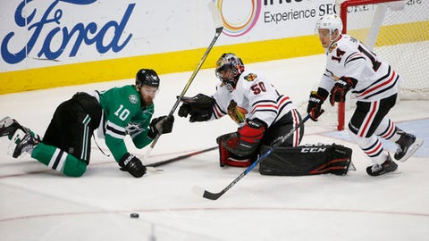 Chicago Blackhawks goalie Corey Crawford (50) makes a save on a shot by Dallas Stars center Martin Hanzal (10) as Blackhawks right wing Richard Panik (14) chases the blocked shot, during the third period of an NHL hockey game in Dallas, Thursday, Dec. 21, 2017. The Stars won 4-0. (AP Photo/Michael Ainsworth)