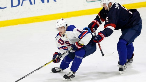 In this Sunday, Dec. 17, 2017 photo, United States' Ryan Lindgren, right, checks Kailer Yamamoto during hockey practice in Columbus, Ohio. Expectations will be high when the US under-20 team defends its title on home soil at the World Junior tournament, starting the day after Christmas in Buffalo, N.Y. (AP Photo/Jay LaPrete)