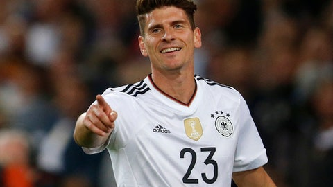 In this Monday, Sept. 4, 2017 photo Germany's Mario Gomez celebrates after scoring his side's sixth goal during the World Cup Group C qualifying soccer match between Germany and Norway in Stuttgart, Germany. Gomez leaves his current German first division, Bundesliga, club VfL Wolfsburg and signed a contract with his former club VfB Stuttgart with a contract duration until 2020. (AP Photo/Michael Probst)
