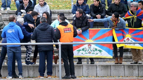 FILE - In this Nov. 18, 2017 file photo a Chinese spectator attempts to tear away a Tibetian flag which was raised by others in protest of China's politics regarding Tibet at the friendly match between TSV Schott Mainz and China's U20 team at the regional sports facility in Mainz, Germany. The German and Chinese soccer federations have abandoned a series of friendly games by the China under-20 team against fourth-tier clubs in Germany following a controversy over spectators displaying Tibetan flags.  (Hasan Bratic/dpa via AP,file)