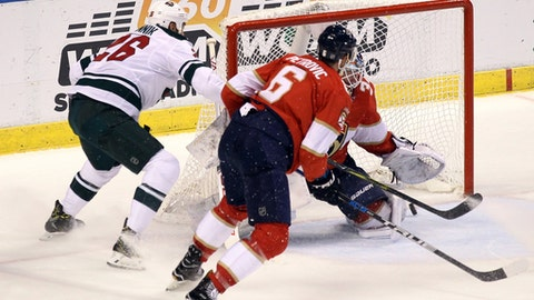 Minnesota Wild's Daniel Winnik, left, scores a goal against Florida Panthers goalie James Reimer as Panthers' Alex Petrovic (6) defends during the second period of an NHL hockey game, Friday, Dec. 22, 2017, in Sunrise, Fla. (AP Photo/Luis M. Alvarez)