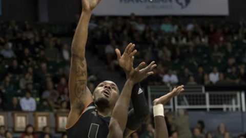 Miami guard Ja'Quan Newton (0) shoots a layup over Hawaii guard Leland Green (0) during the first half of an NCAA college basketball game at the Diamond Head Classic tournament, Friday, Dec. 22, 2017, in Honolulu. (AP Photo/Eugene Tanner)