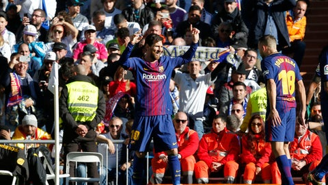 Barcelona's Lionel Messi, left, celebrates after scoring the second goal during a Spanish La Liga soccer match between Real Madrid and Barcelona at the Santiago Bernabeu stadium in Madrid, Spain, Saturday, Dec. 23, 2017. (AP Photo/Paul White)