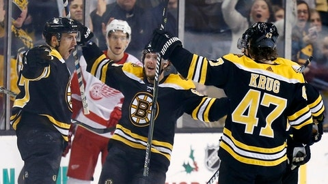 Boston Bruins' Patrice Bergeron, left, celebrates his goal with teammates including Torey Krug (47) during the third period of an NHL hockey game against the Detroit Red Wings in Boston, Saturday, Dec. 23, 2017. The Bruins won 3-1. (AP Photo/Michael Dwyer)