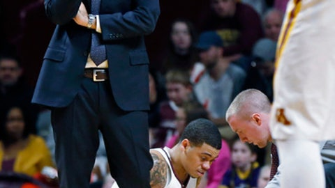 Minnesota head coach Richard Pitino, left, stands by as Nate Mason is attended to after being injured in the second half of an NCAA college basketball game against Florida Atlantic, Saturday, Dec. 23, 2017, in Minneapolis. (AP Photo/Jim Mone)