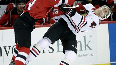 New Jersey Devils left wing Taylor Hall, left, hits Chicago Blackhawks defenseman Gustav Forsling (42), of Sweden, during the second period of an NHL hockey game, Saturday, Dec. 23, 2017, in Newark, N.J. (AP Photo/Julio Cortez)