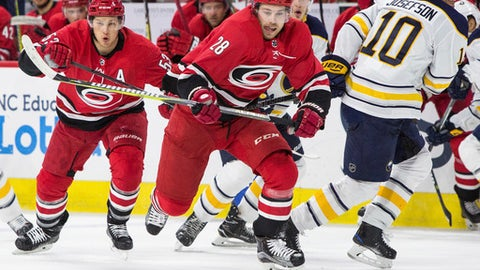 Carolina Hurricanes' Elias Lindholm (28), of Sweden, skates towards the puck ahead of teammate Jeff Skinner (53) and Buffalo Sabres' Jacob Josefson (10), also of Sweden, during the second period of an NHL hockey game in Raleigh, N.C., Saturday, Dec. 23, 2017. (AP Photo/Ben McKeown)