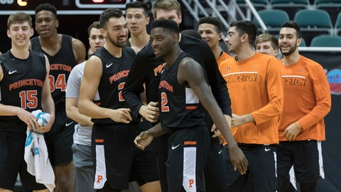 Princeton guard Myles Stephens, center, is congratulated by his teammates after shooting the game winning shot over Akron during the second half of an NCAA college basketball game at the Diamond Head Classic tournament, Saturday, Dec. 23, 2017, in Honolulu. Princeton beat Akron 64-62. (AP Photo/Eugene Tanner)