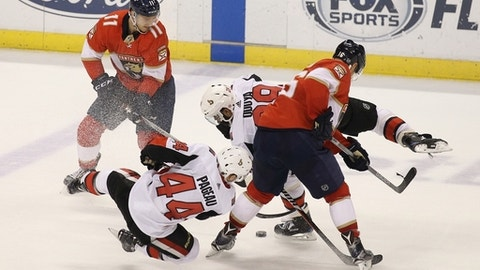 Florida Panthers' Jonathan Huberdeau (11) and Aleksander Barkov, right, of Finland, look for the puck as Ottawa Senators' Jean-Gabriel Pageau (44) and Johnny Oduya, center, of Sweden, defend during the third period of an NHL hockey game, Saturday, Dec. 23, 2017, in Sunrise, Fla. (AP Photo/Luis M. Alvarez)