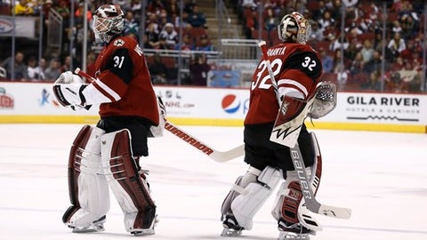 Having given up three goals to the Colorado Avalanche, Arizona Coyotes goalie Antti Raanta (32) is replaced by Scott Wedgewood (31) during the second period of an NHL hockey game Saturday, Dec. 23, 2017, in Glendale, Ariz. (AP Photo/Ross D. Franklin)