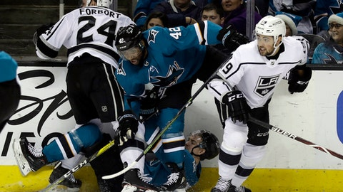 San Jose Sharks' Joel Ward (42) gets tangled against the boards with teammate Mikkel Boedker, bottom center, and Los Angeles Kings defenseman Derek Forbort (24) and center Alex Iafallo, right, during the second period of an NHL hockey game Saturday, Dec. 23, 2017, in San Jose, Calif. (AP Photo/Marcio Jose Sanchez)