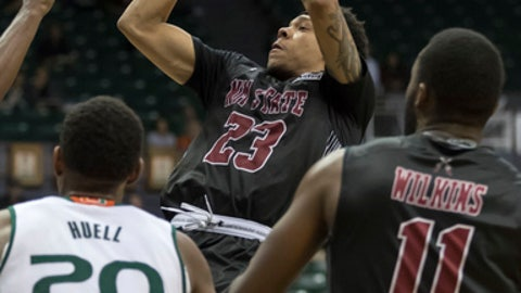 New Mexico State guard Zach Lofton (23) shoots as forward Johnathon Wilkins (11) and Miami forward Dewan Huell (20) watch during the second half of an NCAA college basketball game at the Diamond Head Classic tournament, Saturday, Dec. 23, 2017, in Honolulu. New Mexico State upset Miami, 63-54. (AP Photo/Eugene Tanner)