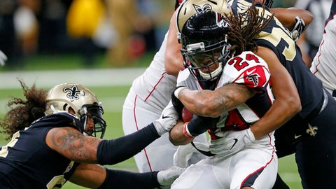 Atlanta Falcons running back Devonta Freeman (24) is tackled by New Orleans Saints outside linebacker Craig Robertson (52) and outside linebacker Hau'oli Kikaha, left, in the first half of an NFL football game in New Orleans, Sunday, Dec. 24, 2017. (AP Photo/Butch Dill)