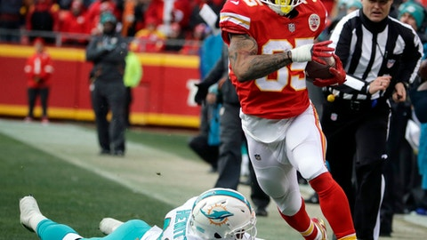 Kansas City Chiefs running back Charcandrick West (35) runs past a tackle-attempt by Miami Dolphins linebacker Neville Hewitt (46) during the second half of an NFL football game in Kansas City, Mo., Sunday, Dec. 24, 2017. (AP Photo/Charlie Riedel)