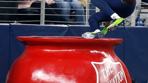 Seattle Seahawks cornerback Justin Coleman (28) leaps into The Salvation Army kettle after returning a Dallas Cowboys' Dak Prescott interception for a touchdown in the second half of an NFL football game, Sunday, Dec. 24, 2017, in Arlington, Texas. (AP Photo/Michael Ainsworth)