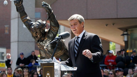 "FILE - In this May 10, 2010, file photo, Boston Bruins hockey great Bobby Orr addresses a crowd during an unveiling ceremony for a statue of Orr, left, in front of the TD Garden sports arena, in Boston. The statue depicts Orr in the defining moment when he scored in overtime in 1970 giving the Bruins victory over the St. Louis Blues to win the Stanley Cup. As the NHL celebrates its 100th anniversary, Orr's goal is so important that it reached the finals of the ""Greatest Moments"" bracket 47 years after it happened. (AP Photo/Steven Senne, File)"