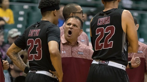 New Mexico State head coach Chris Jans shouts instructions to guard Zach Lofton (23) as forward Eli Chuha (22) looks on during the first half of an NCAA college basketball game at the Diamond Head Classic, Monday, Dec. 25, 2017, in Honolulu. (AP Photo/Eugene Tanner)