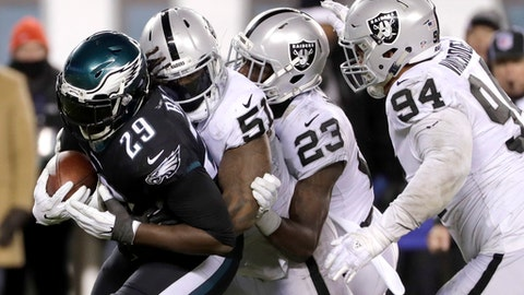 Philadelphia Eagles' LeGarrette Blount (29) is tackled by Oakland Raiders' Bruce Irvin (51), Dexter McDonald (23) and Eddie Vanderdoes (94) during the second half of an NFL football game, Monday, Dec. 25, 2017, in Philadelphia. (AP Photo/Michael Perez)