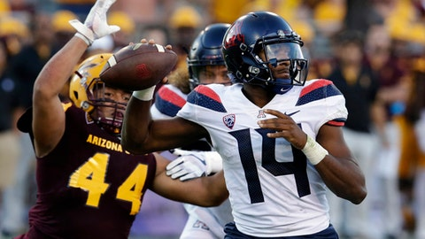 FILE - In this Nov 25, 2017, file photo, Arizona quarterback Khalil Tate (14) throws while getting pressured by Arizona State linebacker Alani Latu during the second half of an NCAA college football game, in Tempe, Ariz. Purdue plays Arizona in the Foster Farms Bowl on Wednesday, Dec. 27. (AP Photo/Rick Scuteri, File)