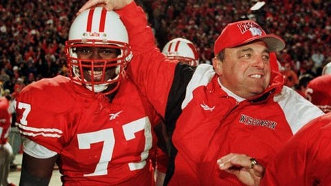 "File- This Nov. 21, 1998 file photo shows Wisconsin's coach Barry Alvarez congratulating Wendell Bryant on the sidelines near the end of the game against Penn State, in Madison, Wis.  Freshman Jonathan Taylor is the latest star to emerge at Wisconsin (12-1), where the ground game traces its roots to the 1990s and Barry Alvarez's days pacing the sideline as head coach. ""That's first of all our philosophy, is we're going to be a physical team, we're going to run the ball, be able to run the ball and it starts with the offensive line,"" said Alvarez, now Wisconsin's athletic director. ""Backs, they want to come where they can run the ball."" (AP Photo/Andy Manis, File)"