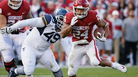 File- This Nov. 25, 2017, file photo shows Oklahoma running back Rodney Anderson (24) carrying in the second quarter of an NCAA college football game against West Virginia in Norman, Okla. Oklahoma's top running back, Anderson, has cleared legal trouble and is now available to play in the Rose Bowl against Georgia. Even if he wasn't, the Sooners are loaded at the position. Trey Sermon, Abdul Adams and Marcelias Sutton all have been significant contributors for a productive ground attack that has kept the pressure off Heisman winning quarterback Baker Mayfield. (AP Photo/Sue Ogrocki, File)