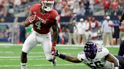 File- This Dec. 2, 2017, file photo show Oklahoma running back Trey Sermon (4) escaping a tackle attempt by TCU defensive tackle Chris Bradley (56) in the first half of the Big 12 Conference championship NCAA college football game in Arlington, Texas.  Oklahoma's top running back, Rodney Anderson, has cleared legal trouble and is now available to play in the Rose Bowl against Georgia. Even if he wasn't, the Sooners are loaded at the position. Sermon, Abdul Adams and Marcelias Sutton all have been significant contributors for a productive ground attack that has kept the pressure off Heisman winning quarterback Baker Mayfield.(AP Photo/Tony Gutierrez, File)