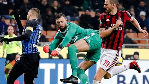 AC Milan goalkeeper Antonio Donnarumma, center, blocks Inter Milan's Mauro Icardi, left, as teammate Leonardo Bonucci, right, defends during an Italian Cup quarter-final soccer match between Milan and Inter Milan at the San Siro stadium in Milan, Italy, Wednesday, Dec. 27, 2017. (AP Photo/Antonio Calanni)