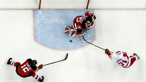 New Jersey Devils goalie Cory Schneider, center, stops a shot by Detroit Red Wings center Dylan Larkin, right, as Steven Santini (16) helps on defense during the first period of an NHL hockey game Wednesday, Dec. 27, 2017, in Newark, N.J. (AP Photo/Julio Cortez)
