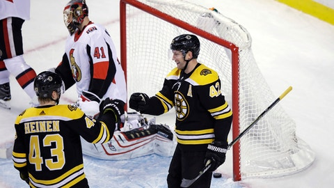 Boston Bruins right wing David Backes (42) is congratulated by Danton Heinen (43) after his goal off Ottawa Senators goalie Craig Anderson (41) during the third period of an NHL hockey game in Boston, Wednesday, Dec. 27, 2017. The Bruins defeated the Senators 5-1. (AP Photo/Charles Krupa)