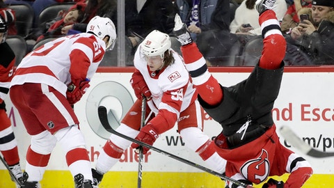 New Jersey Devils center Nico Hischier, right, of Switzerland, flips over while competing for the puck with Detroit Red Wings' Tyler Bertuzzi (59) and Frans Nielsen (51), of Denmark, during the second period of an NHL hockey game, Wednesday, Dec. 27, 2017, in Newark, N.J. (AP Photo/Julio Cortez)