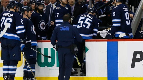 Winnipeg Jets' Mark Scheifele (55) is assisted off the ice during the second period of the team's NHL hockey game against the Edmonton Oilers on Wednesday, Dec. 27, 2017, in Winnipeg, Manitoba. (John Woods/The Canadian Press via AP)