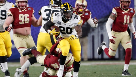 Iowa running back James Butler (20) carries the ball as Boston College defensive back Will Harris (8) tries to stop him during the first half of the Pinstripe Bowl NCAA college football game, Wednesday, Dec. 27, 2017, in New York. (AP Photo/Kathy Willens)