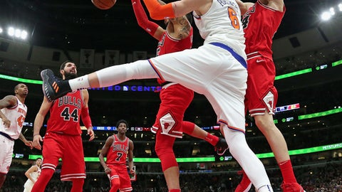 CHICAGO, IL - DECEMBER 27:   Kristaps Porzingis #6 of the New York Knicks battles for a rebound with Denzel Valentine #45 and Luari Markkanen #24 (R) of the Chicago Bulls at the United Center on December 27, 2017 in Chicago, Illinois. The Bulls defeated the Knicks 92-87. NOTE TO USER: User expressly acknowledges and agrees that, by downloading and or using this photograph, User is consenting to the terms and conditions of the Getty Images License Agreement. (Photo by Jonathan Daniel/Getty Images)