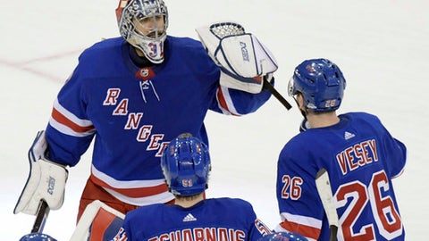 New York Rangers goalie Ondrej Pavelec (31) celebrates with left wing Jimmy Vesey (26) and center David Desharnais (51) after the Rangers defeated the Washington Capitals 1-0 in a shootout of an NHL hockey game, Wednesday, Dec. 27, 2017, at Madison Square Garden in New York. (AP Photo/Bill Kostroun)
