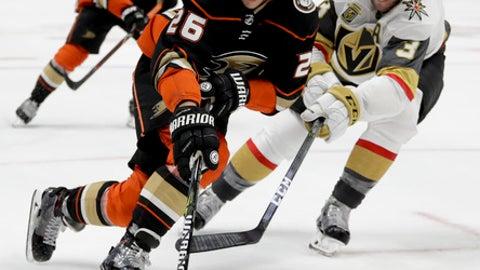 Anaheim Ducks defenseman Brandon Montour, left, reaches for the puck as Vegas Golden Knights' Brayden McNabb defends during the second period of an NHL hockey game in Anaheim, Calif., Wednesday, Dec. 27, 2017. (AP Photo/Chris Carlson)