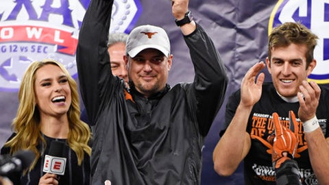 Texas coach Tom Herman, center, lifts the trophy next to Michael Dickson, right, following the team's 33-16 win over Missouri in the Texas Bowl NCAA college football game, Wednesday, Dec. 27, 2017, in Houston. (AP Photo/Eric Christian Smith)