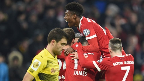 FILE - In this Dec. 20, 2017 file photo, Munich's players, David Alaba on top, celebrate the 2-0 goal during the German DFB (German Football Federation) Cup soccer match between Bayern Munich and Borussia Dortmund in the Allianz Arena in Munich, Germany. (Andreas Gebert/dpa via AP)