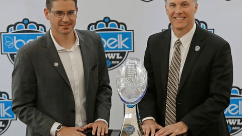 Wake Forest head coach Dave Clawson, right, and Texas A&M interim head coach Jeff Banks, left, pose with the trophy during media day for the Belk Bowl NCAA college football game in Charlotte, N.C., Thursday, Dec. 28, 2017. (AP Photo/Chuck Burton)
