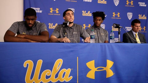 FILE - In this Nov. 15, 2017, file photo, Cody Riley, left, and Jalen Hill, third from left, flank UCLA basketball player LiAngelo Ball as he reads his statement as head coach Steve Alford, far right, listens during a news conference at UCLA  in Los Angeles.  UCLA heads to Shanghai. Shoplifting? Sure, give it a try. Trump tells freed players, please thank me And also thank President Xi. (AP Photo/Jae C. Hong, File)