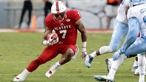 "File- This Nov. 25, 2017, file photo shows North Carolina State's Nyheim Hines (7) running against North Carolina during the first half of an NCAA college football game in Raleigh, N.C. The Wolfpack (8-4) is seeking the second-most wins in school history, and trying to stay in the final College Football Playoff rankings. N.C. State was No. 24 going into bowl season. ""This year it's really important to have a Top 25 finish,""  Hines said. ""We haven't done that yet since I've been here.""  (AP Photo/Gerry Broome, File)"