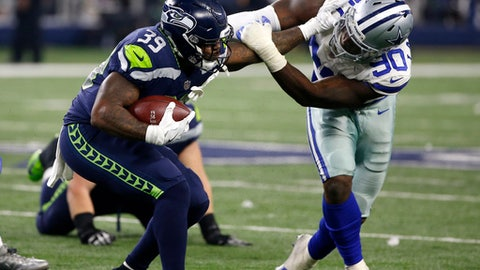 File- This Dec. 24, 2017, file photo shows Seattle Seahawks running back Mike Davis (39) fighting off a tackle attempt by Dallas Cowboys' DeMarcus Lawrence (90) in the second half of an NFL football game in Arlington, Texas. Dallas has pegged him as its next great pass rusher, and he came through in style this season with 14½ sacks. He's the kind of player to build a defensive line around. (AP Photo/Ron Jenkins, File)