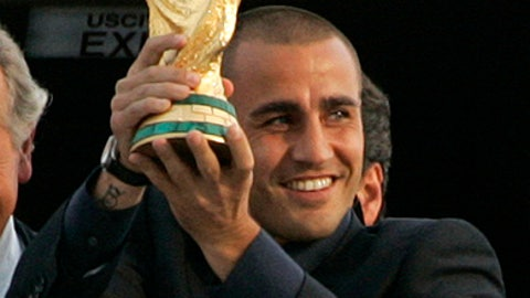 In this Monday, July 10, 2006 file photo, Italy's national soccer team Captain Fabio Cannavaro holds up the trophy he won with his team at the Germany World Cup 2006 upon the team's arrival at Rome's Pratica di Mare military airport, in Rome. Italian defender Paolo Cannavaro announced on Thursday, Dec. 28, 2017 that he will quit soccer after this weekend and join his brother Fabio on the technical staff at Chinese club Guangzhou Evergrande.(AP Photo/Pier Paolo Cito)