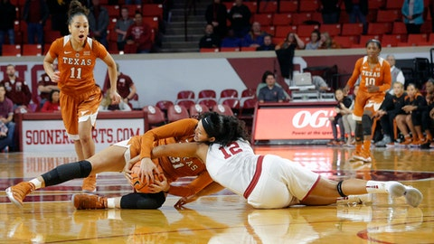 Texas' Audrey-Ann Caron-Goudreau (31) and Oklahoma's Gileysa Penzo (12) fight for the ball during the first half of an NCAA college basketball game in Norman, Okla., Thursday, Dec. 28, 2017. (AP Photo/Garett Fisbeck)