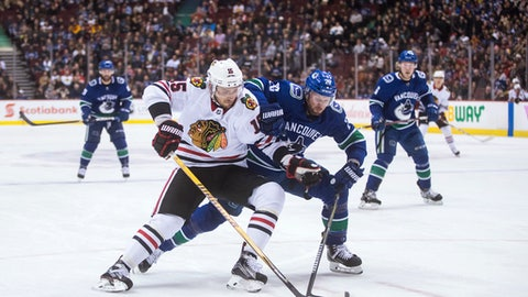 Chicago Blackhawks' Artem Anisimov, left, of Russia, is checked by Vancouver Canucks' Thomas Vanek, of Austria, during the first period of an NHL hockey game Thursday, Dec. 28, 2017, in Vancouver, British Columbia. (Darryl Dyck/The Canadian Press via AP)
