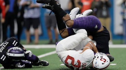 Stanford running back Cameron Scarlett (22) is dropped by TCU safety Innis Gaines, right, after a run during the second half of the Alamo Bowl NCAA college football game, Thursday, Dec. 28, 2017, in San Antonio. (AP Photo/Eric Gay)